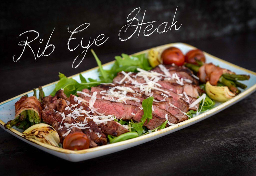 Rib Eye Steak auf Rucolasalat und gehobeltem Parmesan